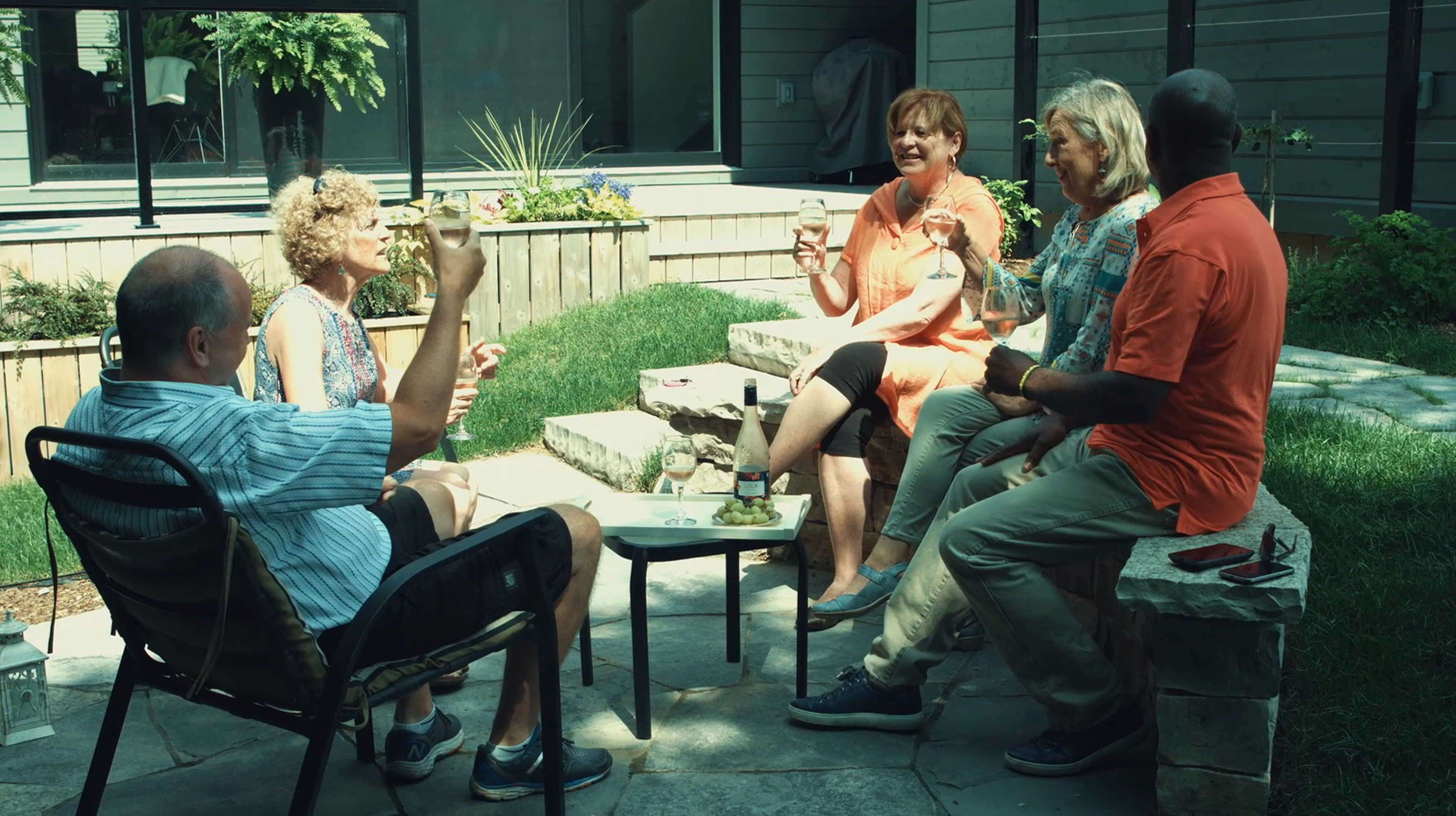A group of adults drinking wine outdoors