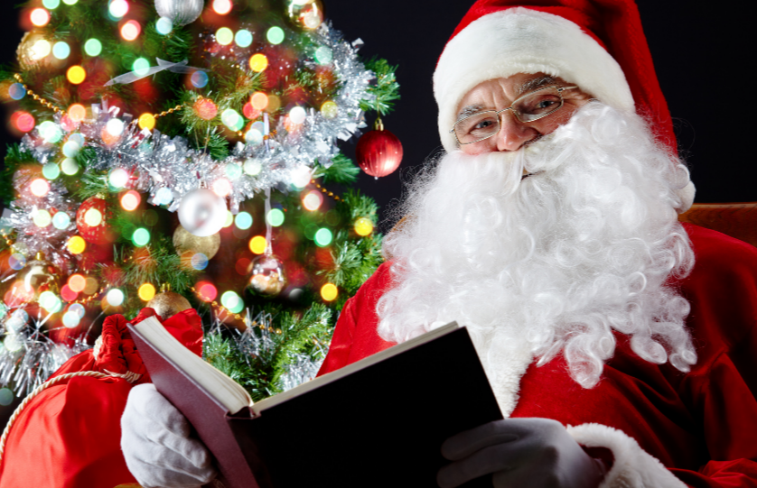 Santa Claus reading a book in front of a Christmas tree