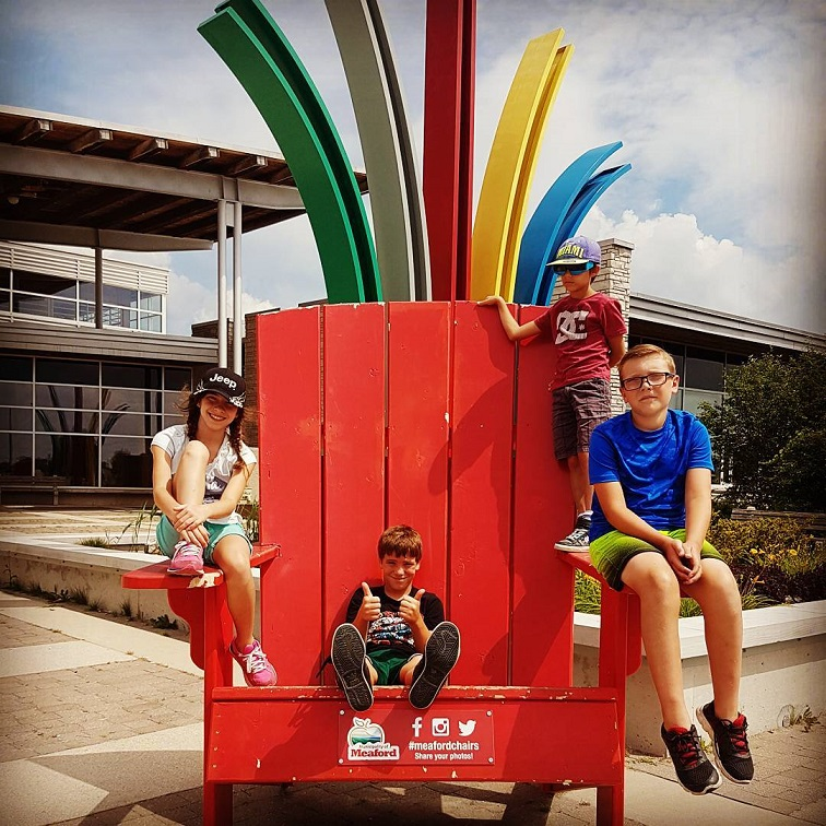 Kids playing on a huge red muskoka chair