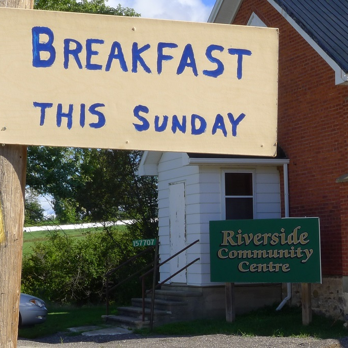 Sign outside a rural community hall reading Breakfast at Riverside