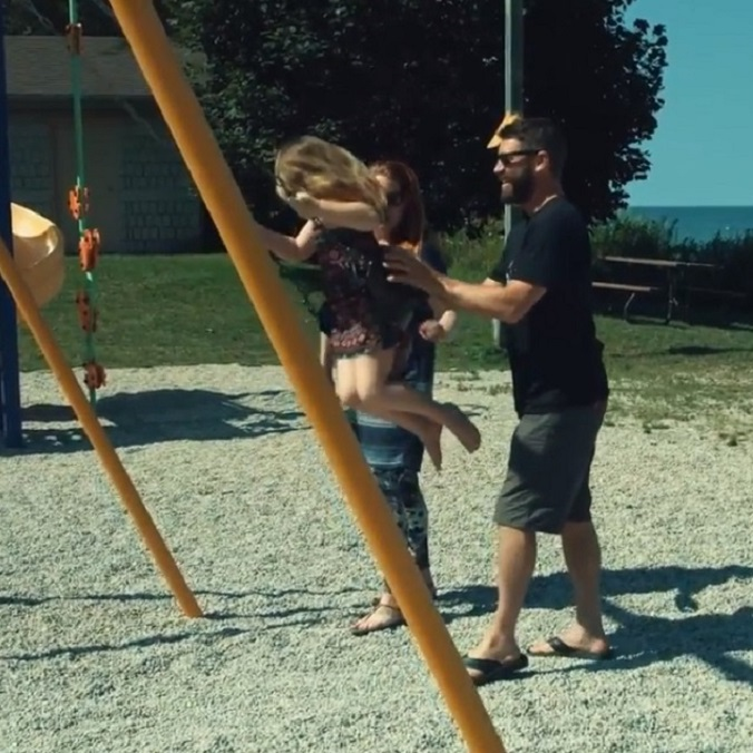 a family playing on a swing set.