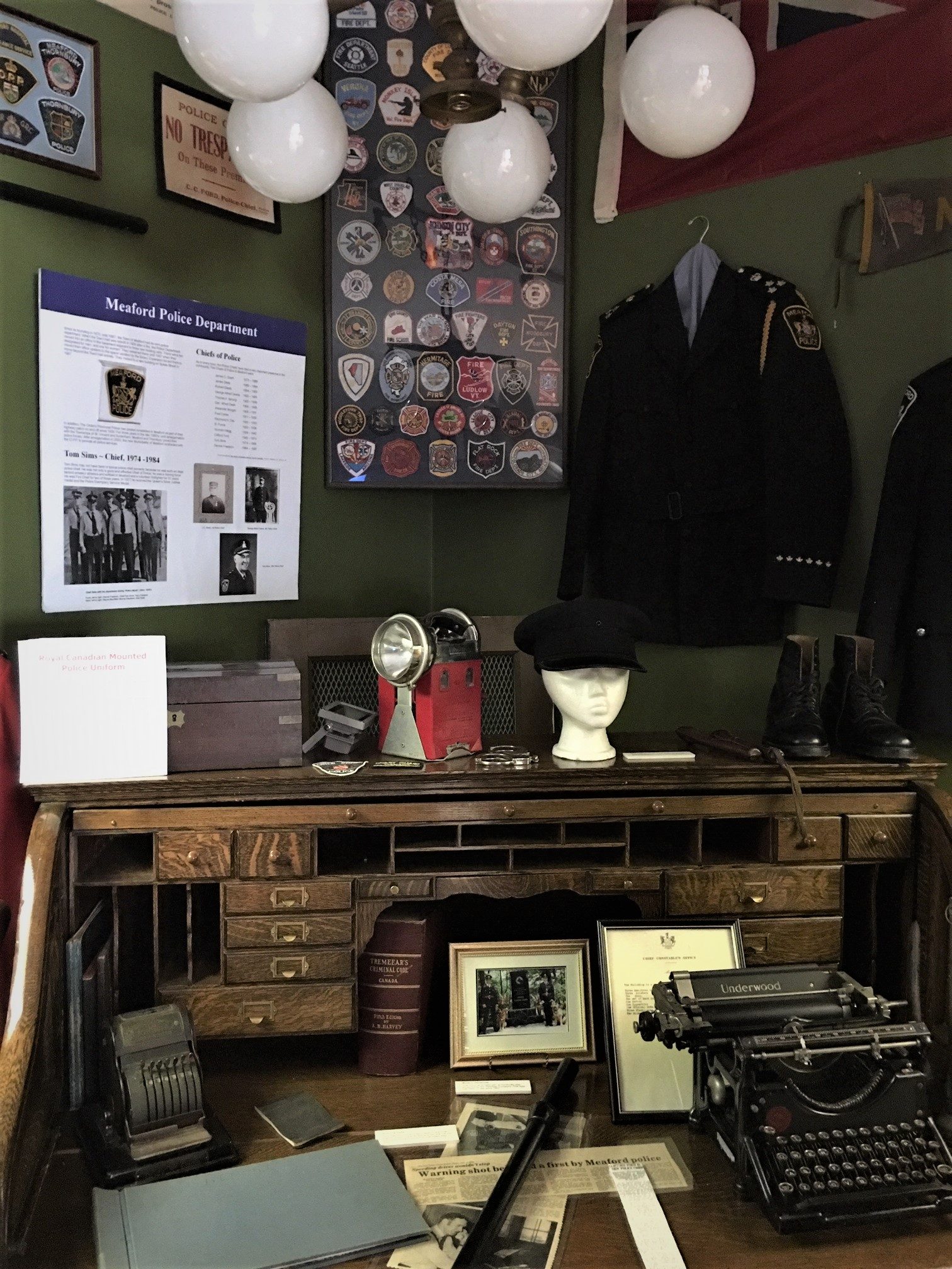 a Museum display with a large antique desk and RCMP and police artifacts