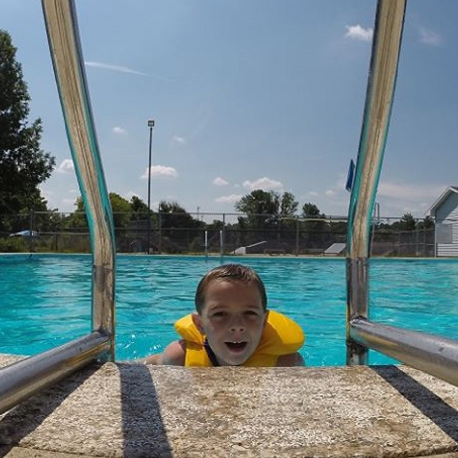 A kid climbing out of the pool